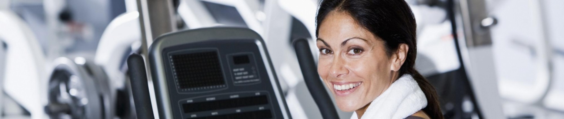 Vrouw zit met handdoek om op de sportschool